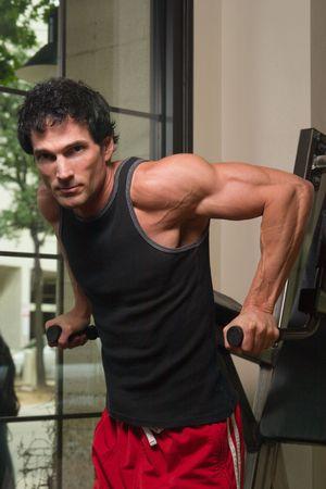 Man de uitoefening van zijn arm spieren op een oefening machine in een fitnesscentrum. Stockfoto