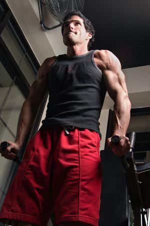 Man, met een vastberaden uitdrukking op zijn gezicht, de uitoefening van zijn arm spieren op een oefening machine in een fitnesscentrum.