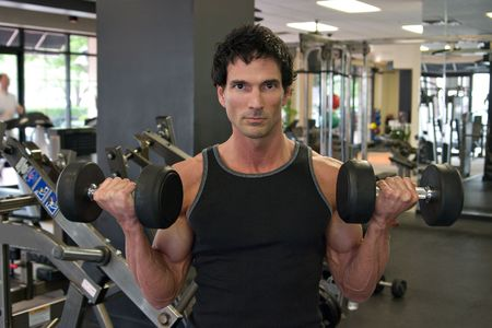Man exercising his arm muscles by lifting two dumbell free weights in a fitness club. Stock Photo