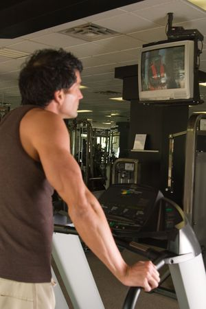 Man working out on a treadmill in a fitness center and watching television while he exercises.  The man is out of focus.  The television he is watching is in focus. photo