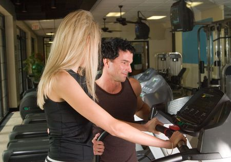 cardiovascular workout: Man and woman exercising together at a fitness center on a treadmill walker exercise machine.  Man could be a personal fitness trainer.
