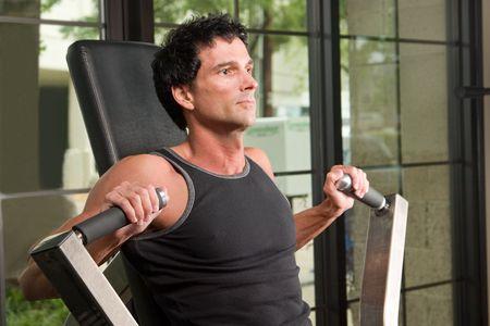 L'uomo esercita il suo braccio muscoli su un esercizio macchina in un centro di fitness.  Archivio Fotografico - 990894