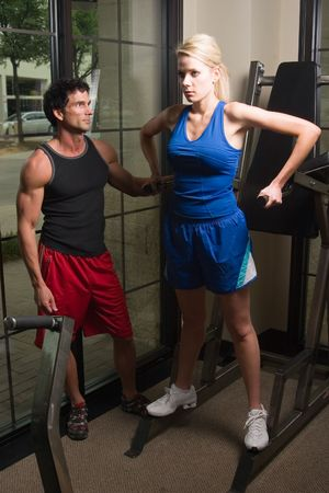 cardiovascular workout: Man and woman exercising together at a fitness center on exercise equipment.  Man could be a personal fitness trainer. Stock Photo