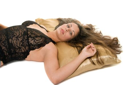 come hither: Beautiful Hispanic woman lying down on satin pillow, looking at the one she loves and wants! Stock Photo