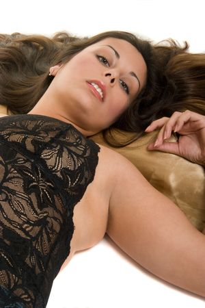 hither: Beautiful Hispanic woman lying down on satin pillow, looking at the one she loves and wants! Stock Photo