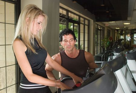 Man and woman exercising together at a fitness center on a treadmill walker exercise machine.  Man could be a personal fitness trainer. photo