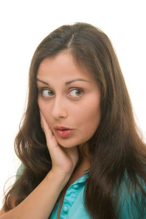 embarassment: Beautiful young brunette woman with one hand on her cheek and a facial expression of surprise, shock, embarassment, or amazement. Stock Photo