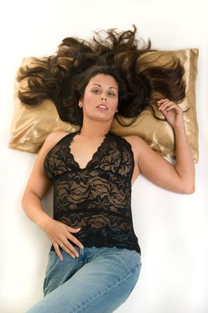 Beautiful Hispanic woman lying down peacefully on satin pillow, relaxing comfortably. photo