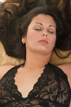 peacefully: Beautiful Hispanic woman lying down peacefully on satin pillow, relaxing and sleeping comfortably. Stock Photo