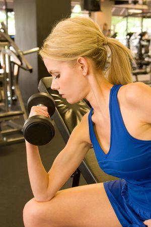 Mooie blonde vrouw tillen gewichten in een fitnesscentrum.