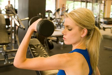 Beautiful blond woman lifting weights in a fitness center.