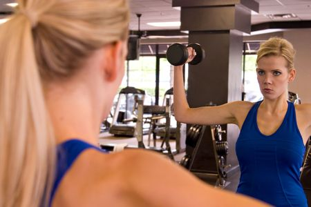 focus on foreground: Beautiful blond woman lifting weights while looking in a mirror in a fitness center. Reflection in mirror is in focus - foreground image is out of focus. Stock Photo