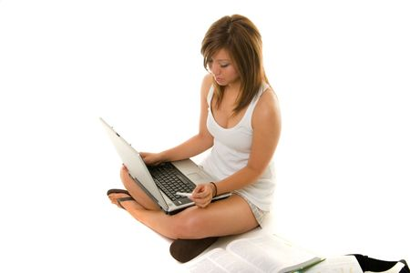 Young Asian girl sitting on the floor studying and working on laptop computer and books. photo