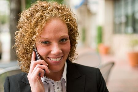 mobilephones: Smiling business woman relaxing on the sidewalk while discussing business on a cellphone.