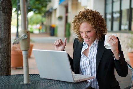 distraught: Young business woman, crushing a coffee cup in one hand, extremely distraught and frustrated with her laptop computer.