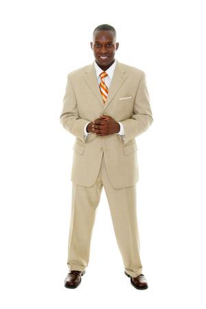 Knap gelukkig lachende man in bruin pak staat met de handen samen. Stockfoto