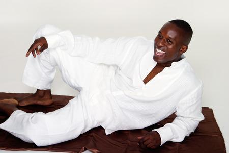 Lachend gelukkig man draagt een wit alle kleding in een ongedwongen liggende houding.