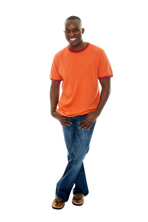 Schone, gelukkig, glimlachende man in een casual outfit van oranje t-shirt, blauwe jeans, en sandalen. Stockfoto