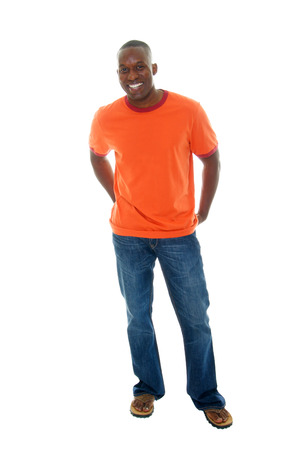 Handsome, happy, smiling man in a casual outfit of orange t-shirt, blue jeans, and sandals. Stock Photo - 1397457