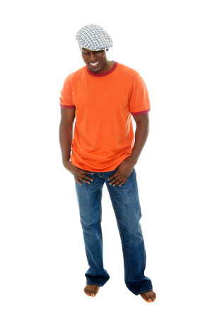 cool guy: Handsome, happy, smiling, barefoot man in a casual outfit of orange t-shirt, blue jeans, and plaid beret. Stock Photo