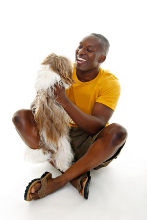 down sitting: Happy casual man holding a happy dog.