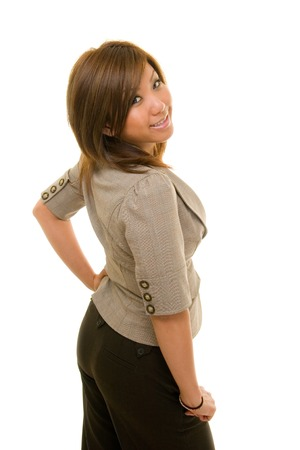 Beautiful young Asian business woman in business suit looks over her right shoulder at the camera photo