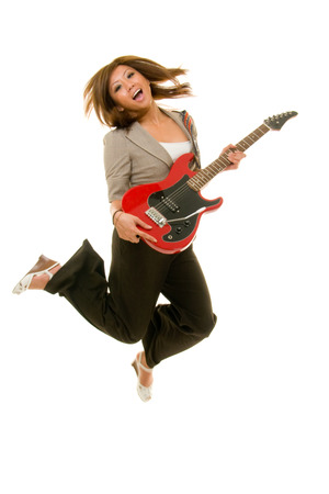 Young Asian adult woman jumping up in the air while playing guitar.  Shot on white. Substantial motion blur from moving, jumping subject. photo