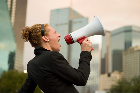 Young business woman making herself heard with a megaphone.
