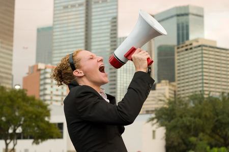 heard: Young business woman making herself heard with a megaphone.