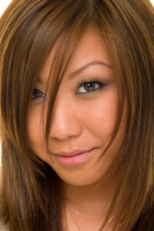 demure: Extreme closeup of a beautiful young Asian brunette woman looking directly into camera.  Shallow depth-of-field with eye and lips in sharp focus. Stock Photo