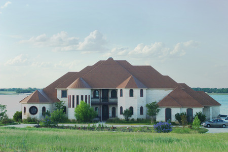 white trim: Large and beautiful modern style house with tile roof and castle turrets on a small lake.