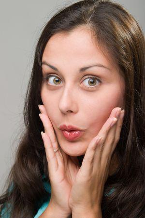 Mooie jonge brunette vrouw met gezichts uitdrukking van verrassing.