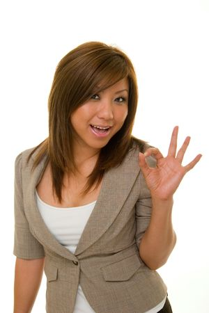 expresses: Beautiful, young Asian woman in business suit expresses A-OK with her hand over accomplishment.