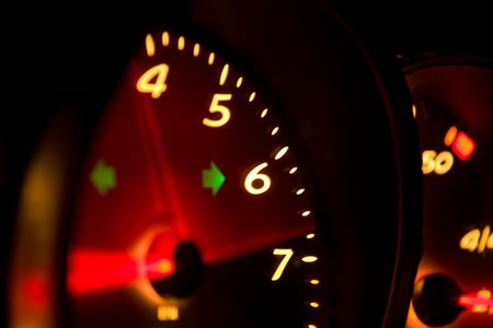 High revving tachometer from a modern high performance automobile glowing at night. Stock Photo