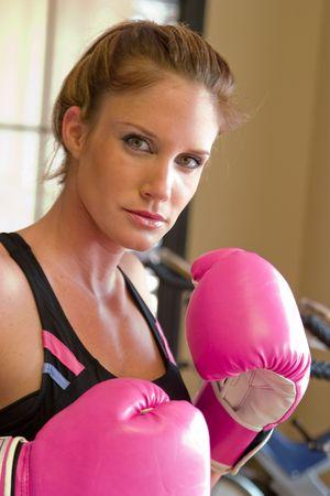krachtige vrouw: Mooi, geschikt vrouw draagt warm roze bokshandschoenen.