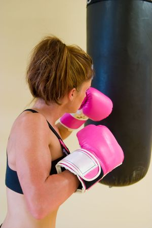 Beautiful boxing girl with pink gloves punching a bag. Stock Photo - 2537522