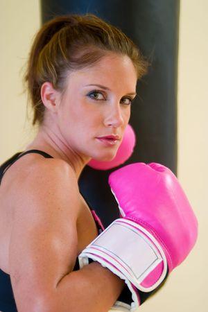 krachtige vrouw: Mooi boksen meisje met roze handschoenen ponsen een tas. Stockfoto