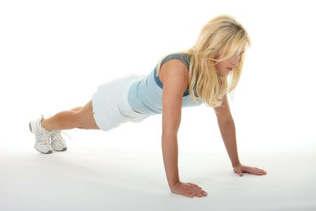 Attractive young blonde woman doing pushups, exercising, and working out.
