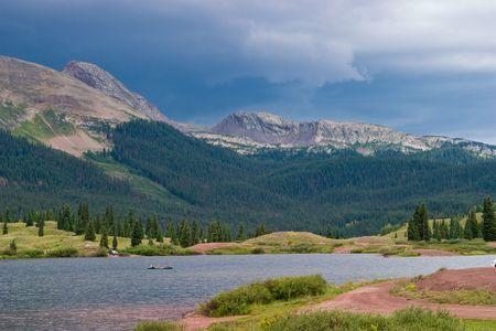 of three are canoeing in Molas Lake near Molas Pass, Colorado as a sudden rain storm approaches. photo