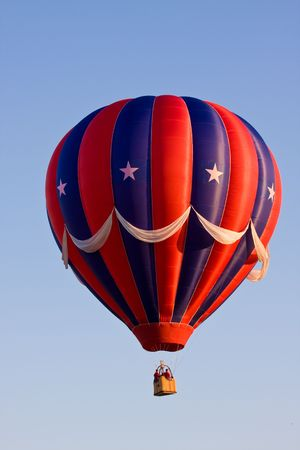 A colorful red, white, and blue patriotic (USA) hot air balloon at a festival is suspended in mid-air on a beautiful clear day. Stock Photo