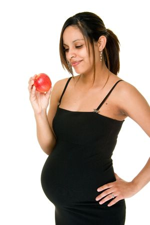 wise woman: A beautiful young pregnant woman in an evening dress makes a healthy choice of an apple for a snack.