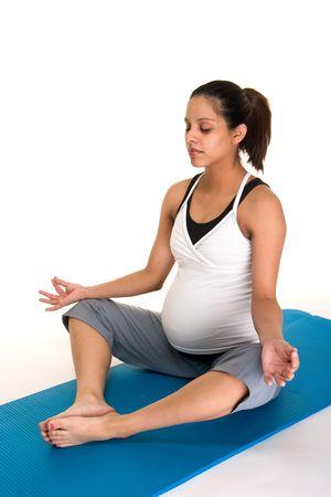 Mooie jonge Spaanse vrouw mediteren in een yoga fitness workout om zichzelf fysiek fit tijdens haar zwangerschap. Shot op een witte achtergrond. Stockfoto