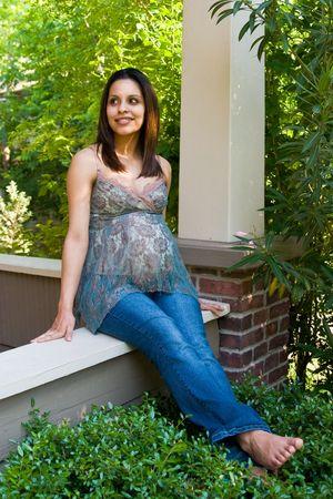 Een mooie jonge vrouw zwanger Hispanic ontspannen buiten witte wachten op de geboorte van haar.