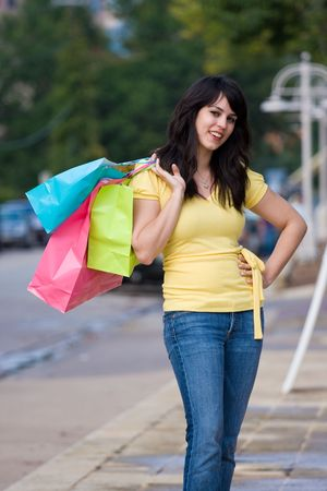 Happy young woman walking down a city sidewalk carrying brightly colored shopping bags. photo