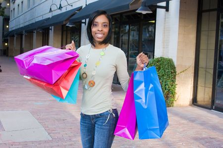 Attractive, young, smiling, African American woman with colorful shopping bags walking in an urban city environment. Stock Photo - 3756427