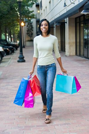 Attractive, young, smiling, African American woman with colorful shopping bags walking in an urban city environment. Stock Photo