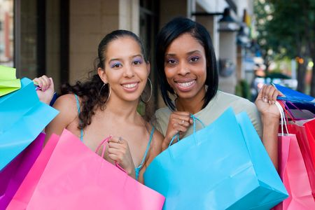 sidewalk sale: Two women friends in the city on a shopping trip carrying colorful shopping bags. Stock Photo