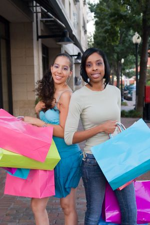 Two women friends in the city on a shopping trip carrying colorful shopping bags. Banco de Imagens