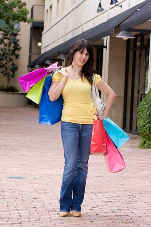 sidewalk sale: Beautiful young brunette woman on a shopping trip in the city carrying colorful shopping bags.