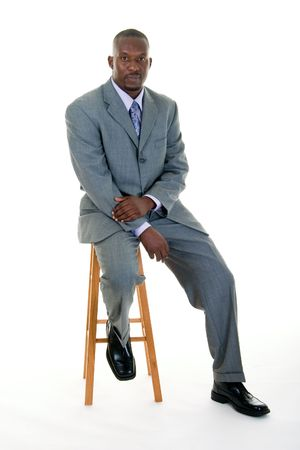 stools: Handsome African American man in a gray business suit sitting on a stool. Stock Photo